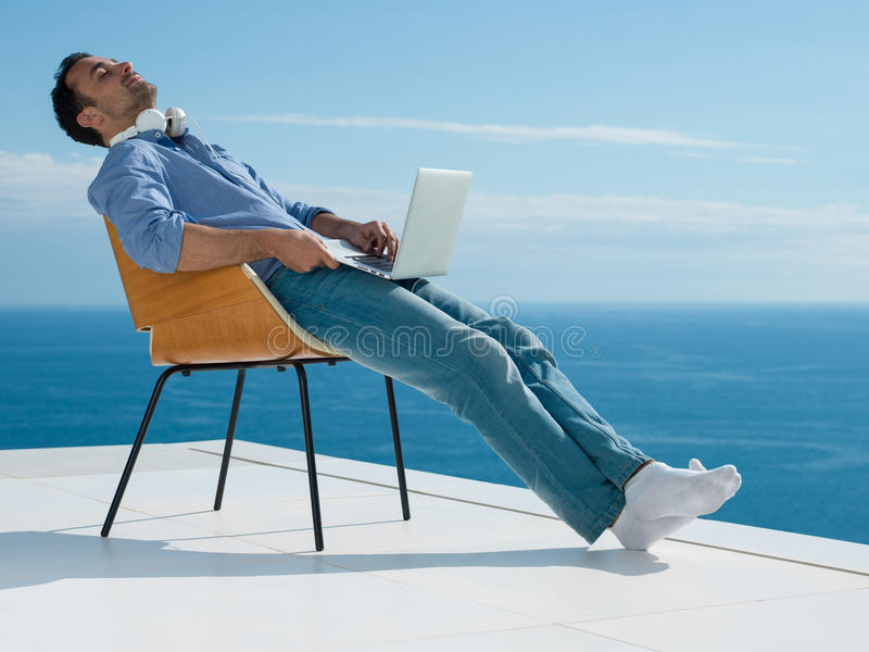 Relaxed young man at home on balcony stock photo
