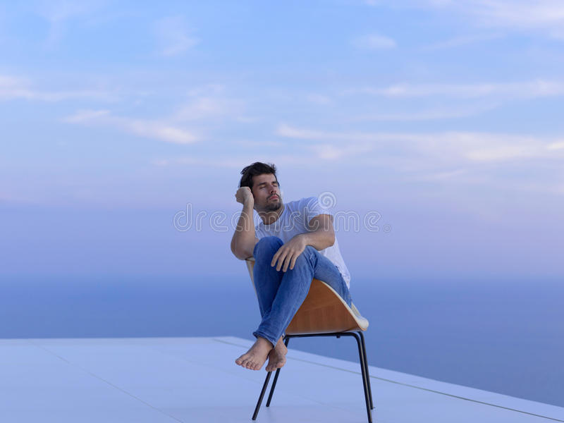 Relaxed young man at home on balcony. Handsome young man relaxing and working on laptop computer at home balcony while looking sunset royalty free stock images