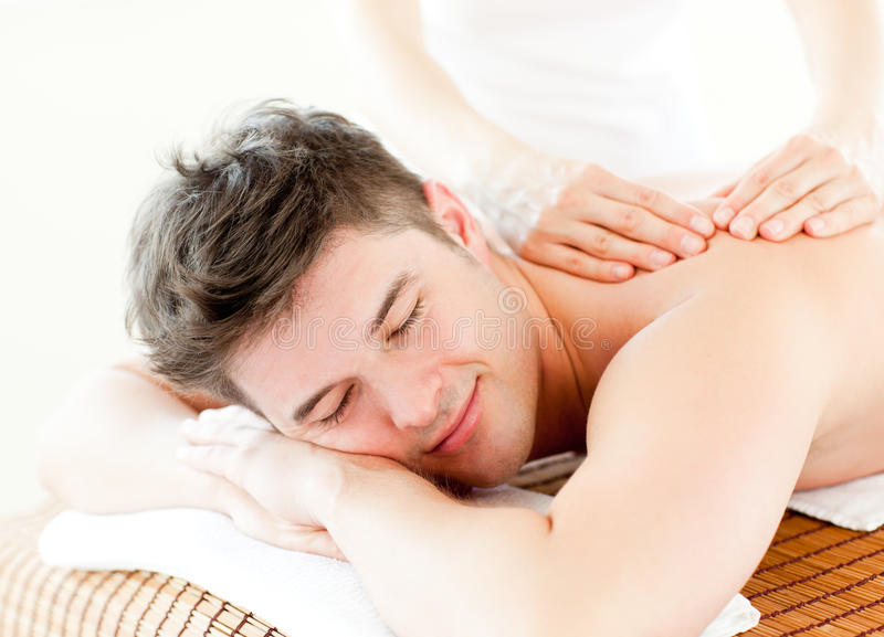 Relaxed young man receiving a back massage stock photo