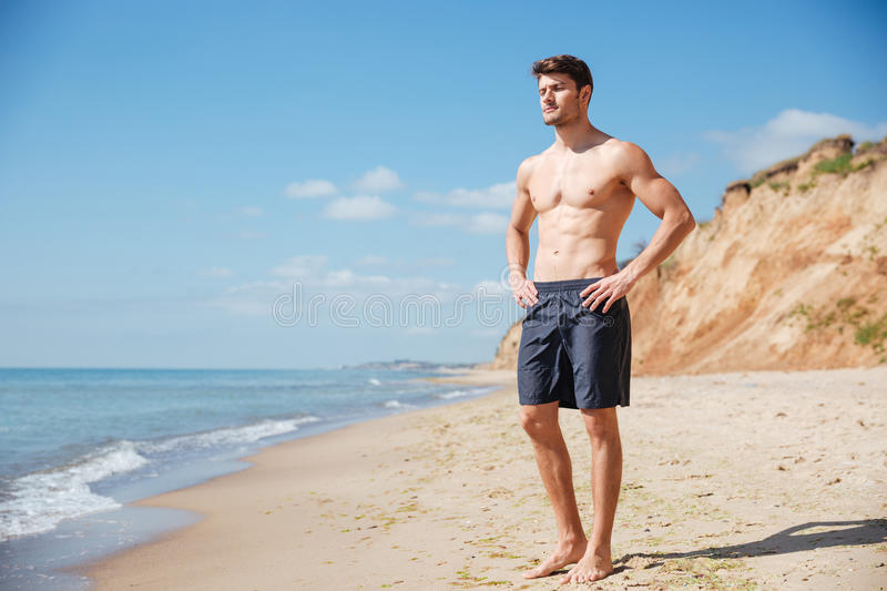 Relaxed young man standing on the beach royalty free stock photo