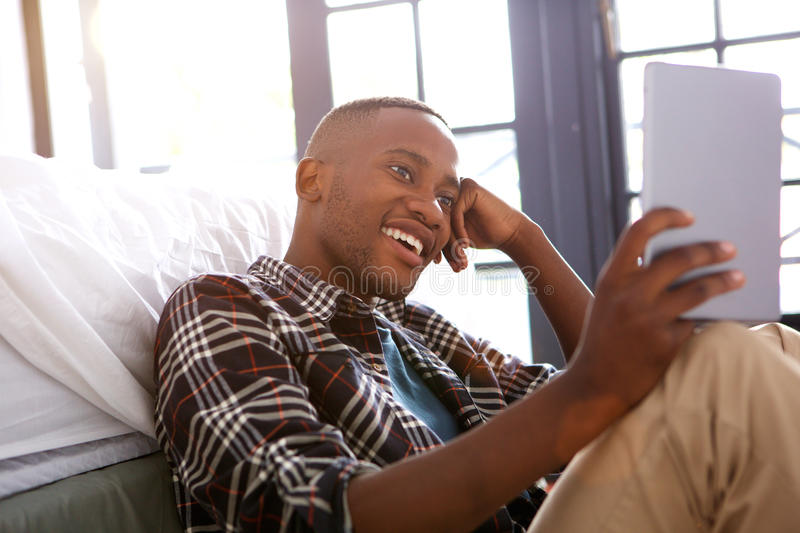Relaxed young man using digital tablet at home stock photography