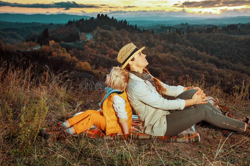 Relaxed young mother and daughter sitting on blanket stock photo