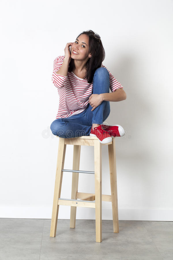 Relaxed young multi-ethnic girl smiling on mobile phone royalty free stock image