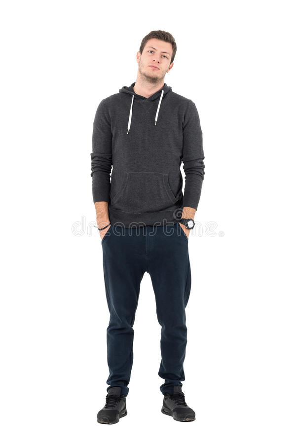 Relaxed young sporty man in hooded sweatshirt and sweatpants looking at camera stock photo