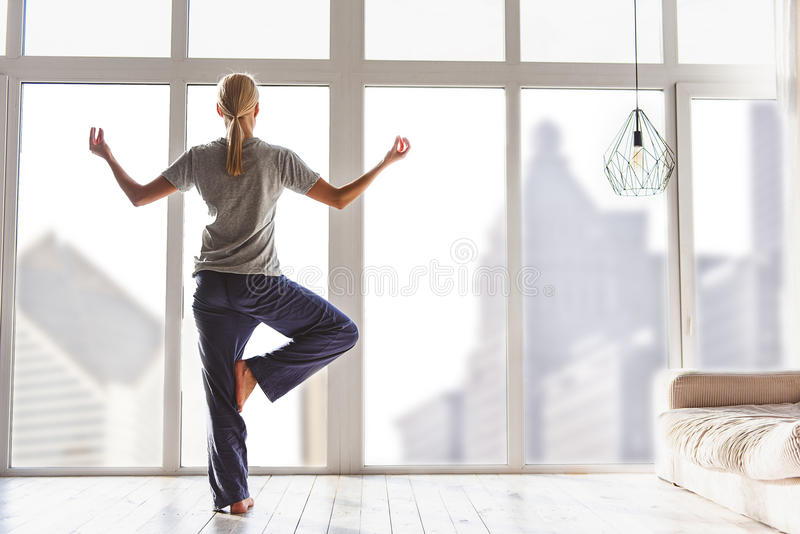 Relaxed young woman exercising at home royalty free stock images