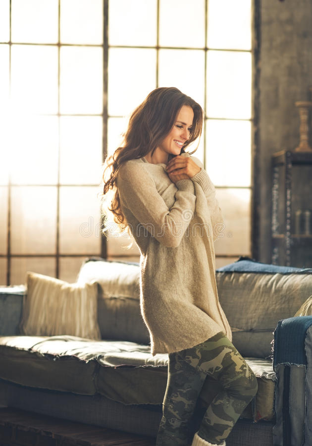 Relaxed young woman in loft apartment royalty free stock image