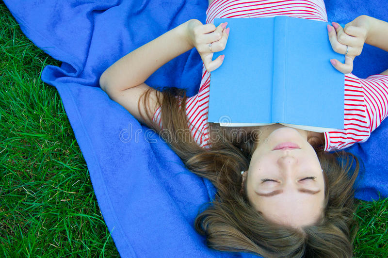 Relaxed young woman reading a book lying on a blanket on the law royalty free stock image