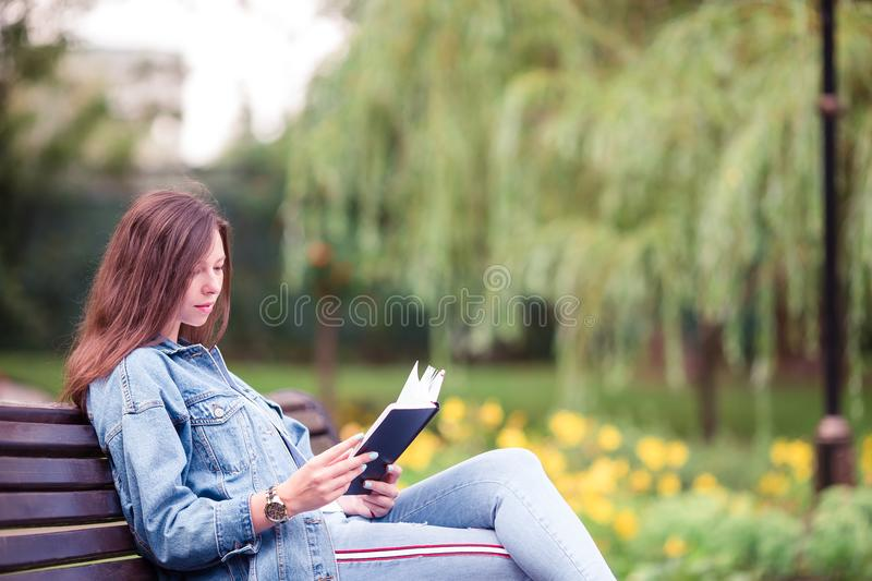 Relaxed young woman reading book stock photo