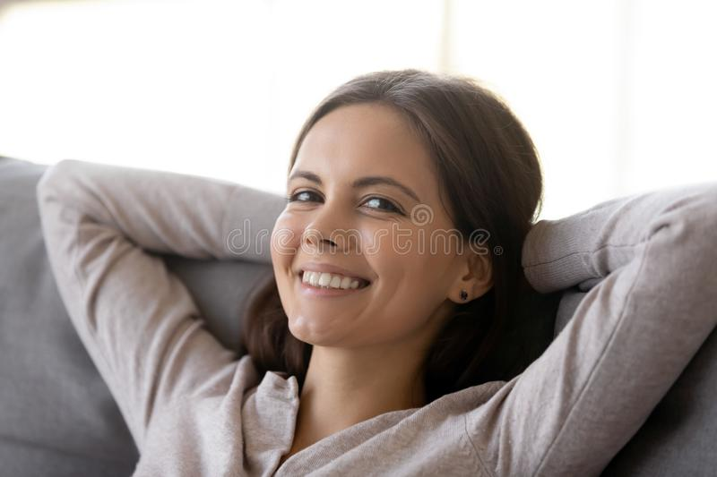 Relaxed young woman resting leaning on couch looking at camera royalty free stock images