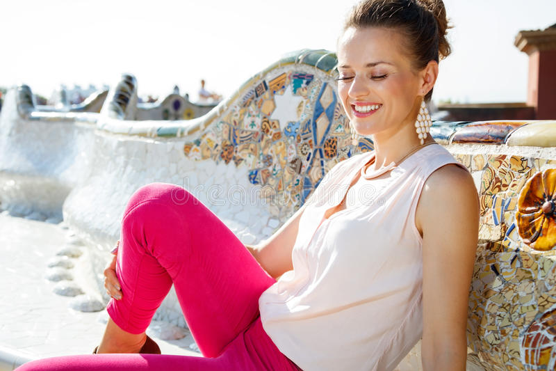 Relaxed young woman sitting on the famous trencadis style bench. Get inspired by Park Guell in your next trip to Barcelona, Spain. Relaxed young woman sitting on stock images