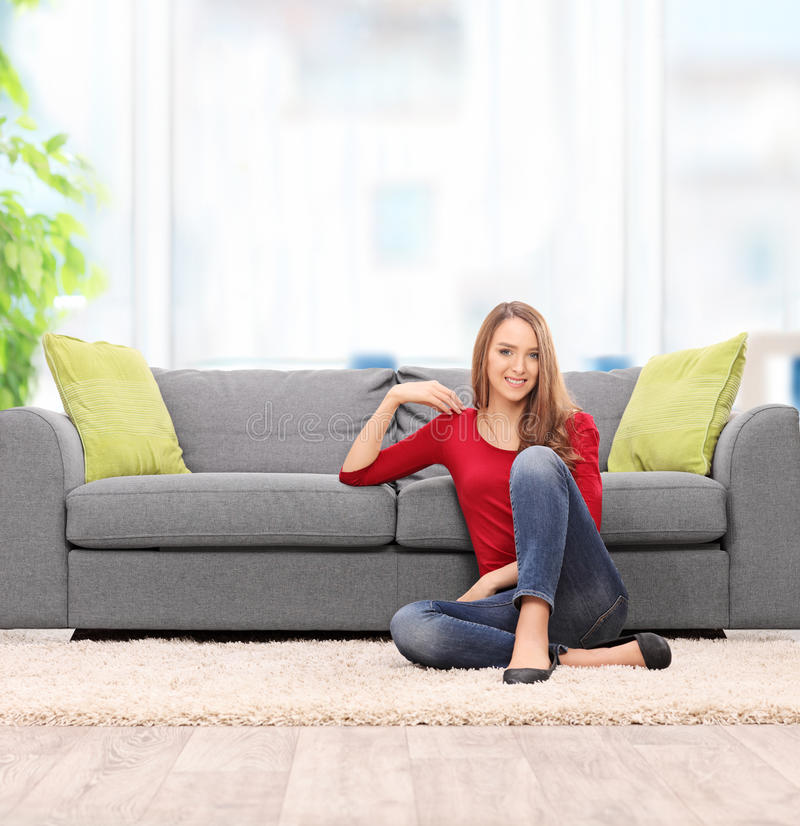 Relaxed young woman sitting by a sofa. At home shot with tilt and shift lens stock images