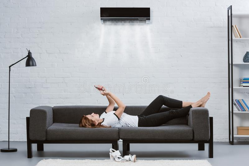 relaxed young woman using smartphone on couch under air conditioner hanging royalty free stock image