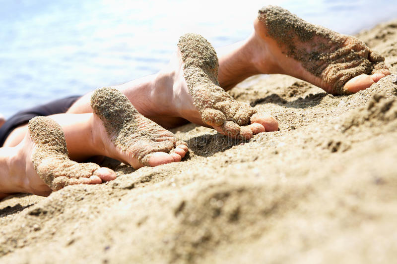 Relaxing. Image of soles of two people lying on sandy beach royalty free stock photography