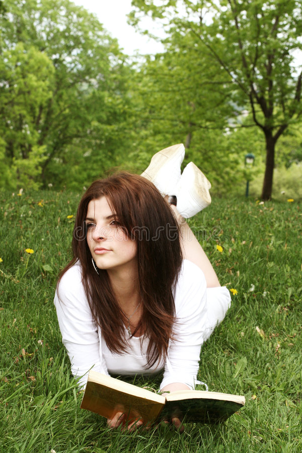 Relaxing. Girl laying in grass with a book royalty free stock photography