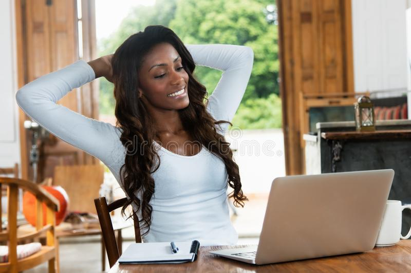 Relaxing african american woman with long hair at computer. R at desk at home stock images
