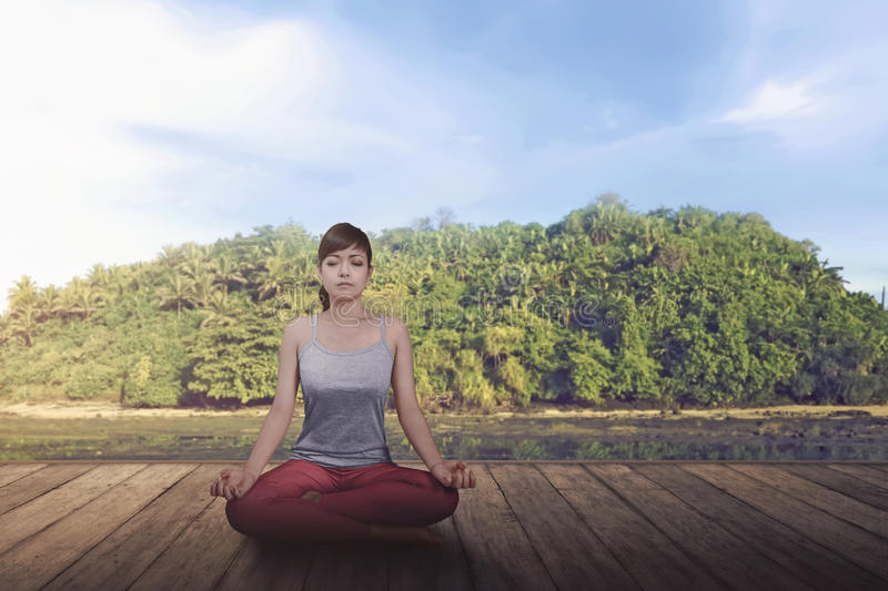 Relaxing asian girl doing yoga in lotus position. On the wooden floor stock photo