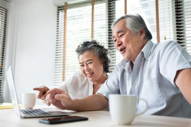 Relaxing Asian Senior couple making video call and talking with family on Laptop computer. Happy Smiling Japanese Elderly man and. Woman enjoy with internet stock photos