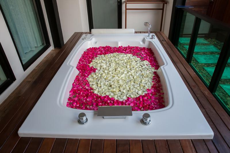 A relaxing bath with rose. bath tub with floating petals. Rose petals put in bathtub for romantic bathroom in honeymoon suit. stock image