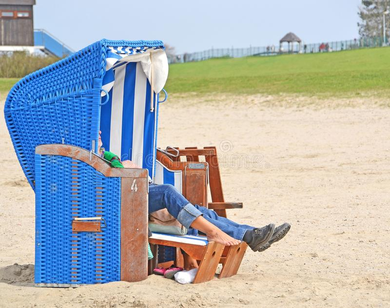 Relaxing at the beach. A couple relaxing in a strandkorb beach chair at the seaside stock images
