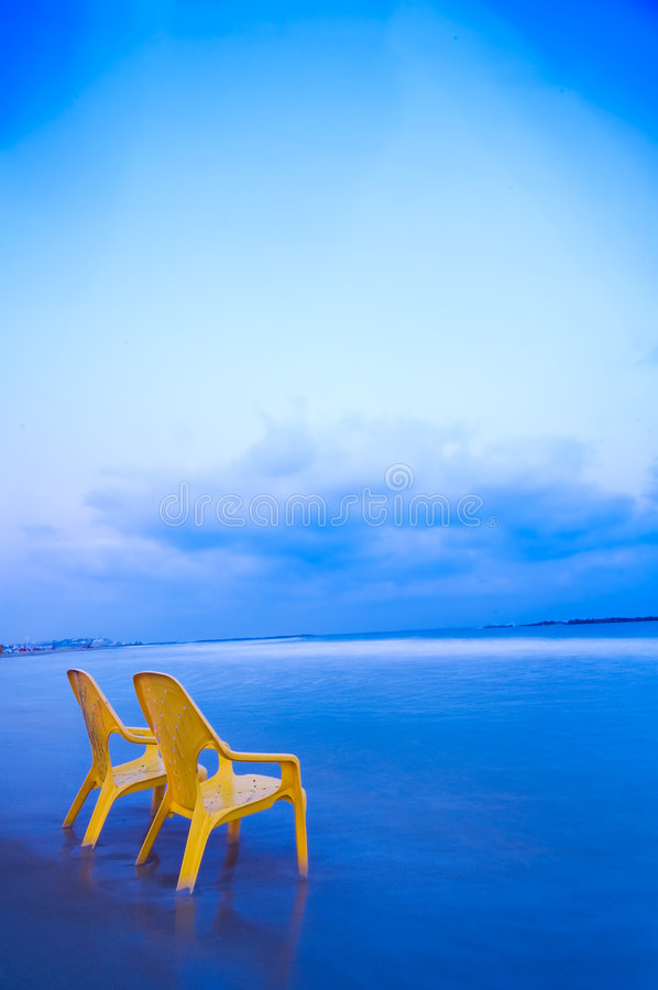 Relaxing at the beach (Vertical). Relaxing at the beach, two yellow chairs, calm blue sea and gentle clouds stock images