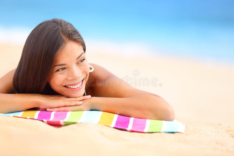 Relaxing beach woman happy. Relaxing beach woman smiling happy looking to the side. Beautiful girl sunbathing under summer sun lying in sand on beach with blue stock photography