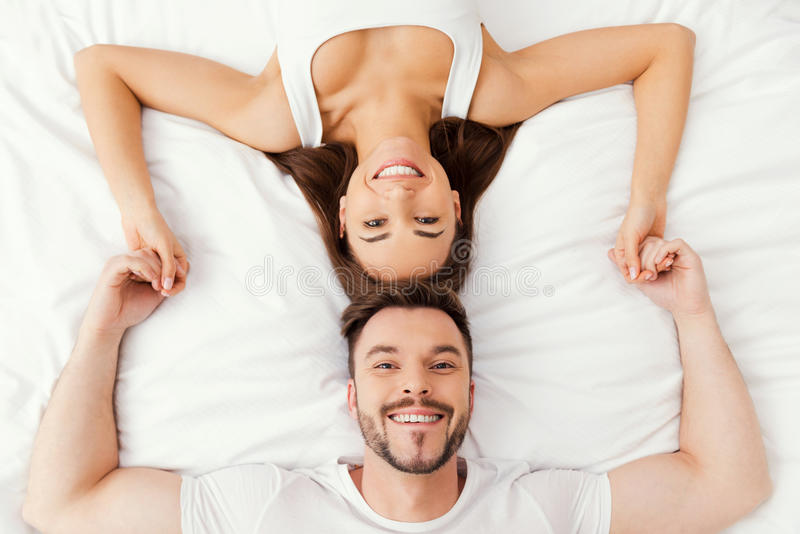 Relaxing in bed together. Top view of beautiful young loving couple lying in bed together and holding hands royalty free stock image