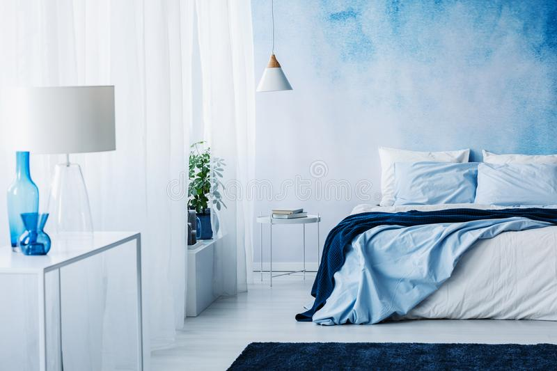 Relaxing bedroom interior with white and blue decorations, double bed and wallpaper stock photography