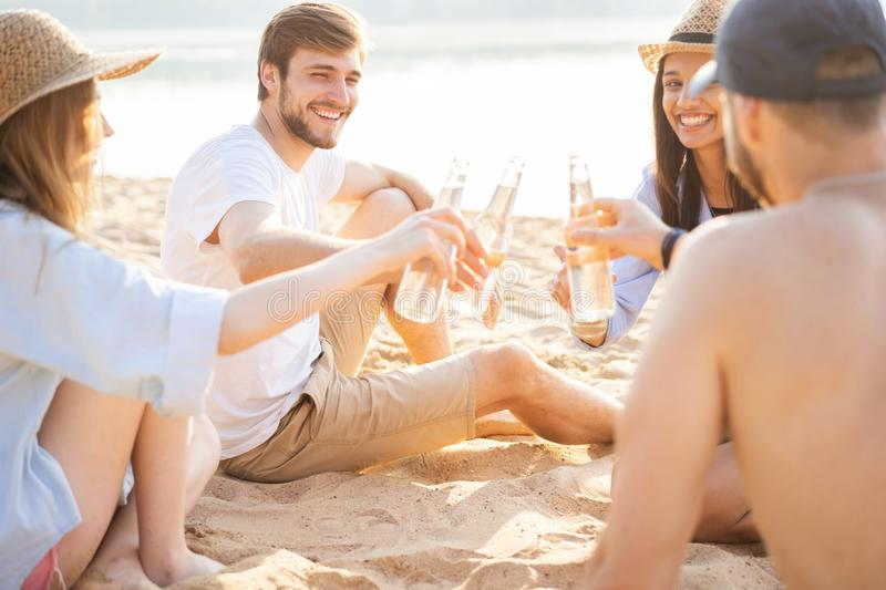 Group of happy young people sitting together at the beach talking and drinking beers royalty free stock photo