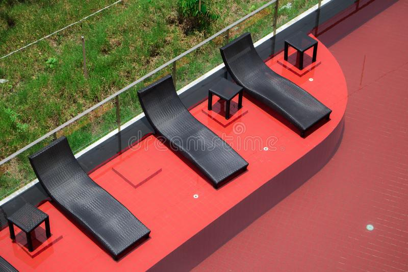 Relaxing black rattan chairs  beside swimming pool royalty free stock photography