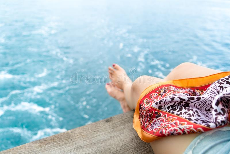 Relaxing blur girl`s leg on the balcony of the blue sea stock image