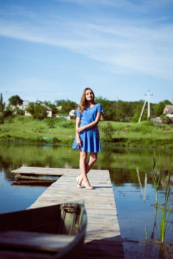 Relaxing brunette young pretty girl in blue dress. Picture of relaxing brunette young pretty girl in blue dress standing on bridge on sunny day royalty free stock photos