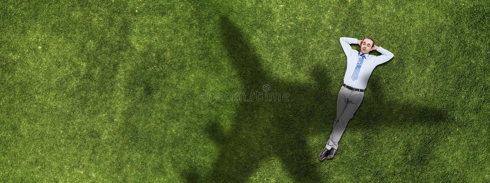 Relaxing businessman on grass royalty free stock images