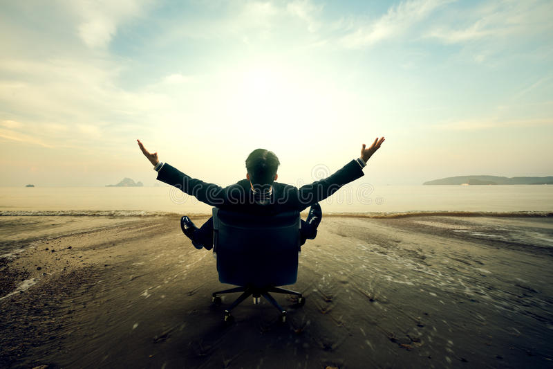 Relaxing businessman sitting on beach. Success in business concept stock photos