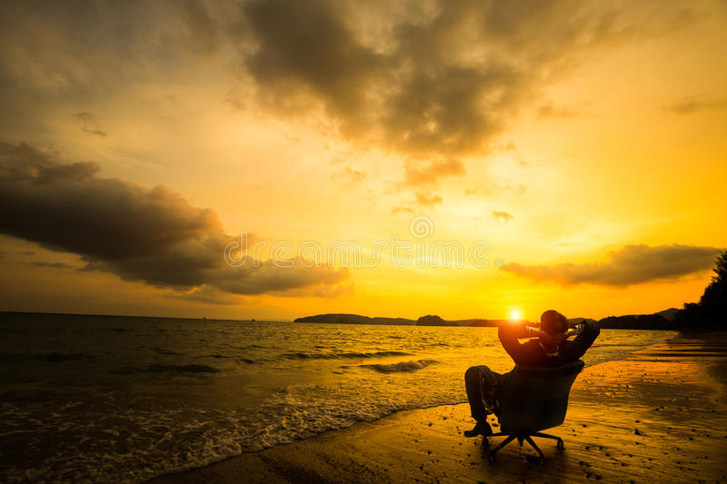 Relaxing businessman sitting on beach. Success in business concept royalty free stock photo