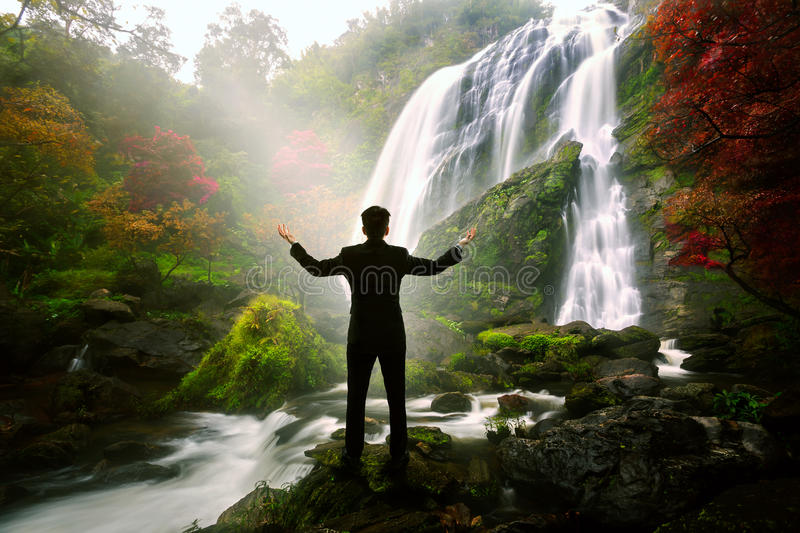 Relaxing businessman standing at waterfall. Success in business concept stock photography