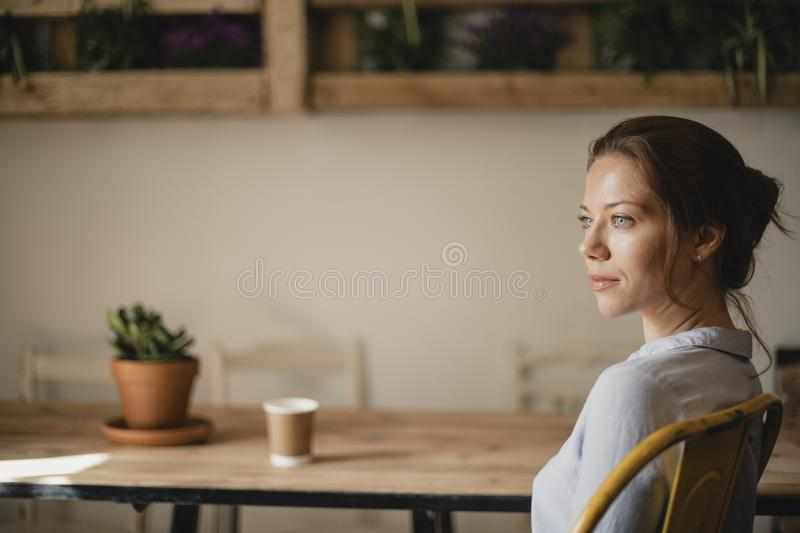 Relaxing in a Cafe. MId adult woman sitting at a take in a small cafe with a disposable coffee cup. She is looking out the window and enjoying the peace and royalty free stock images