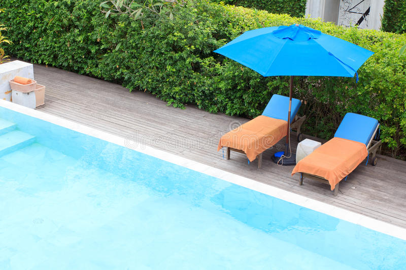 Relaxing chairs beside of swimming pool royalty free stock images