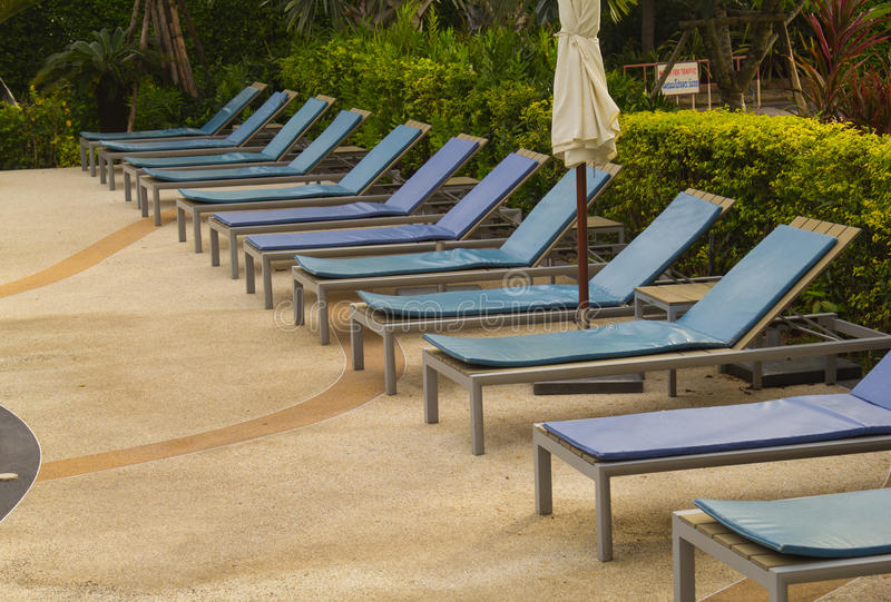 Relaxing chairs beside of swimming pool in hotel royalty free stock photography
