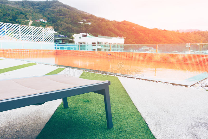 Relaxing chairs with beside swimming pool on top deck hotel. stock photo