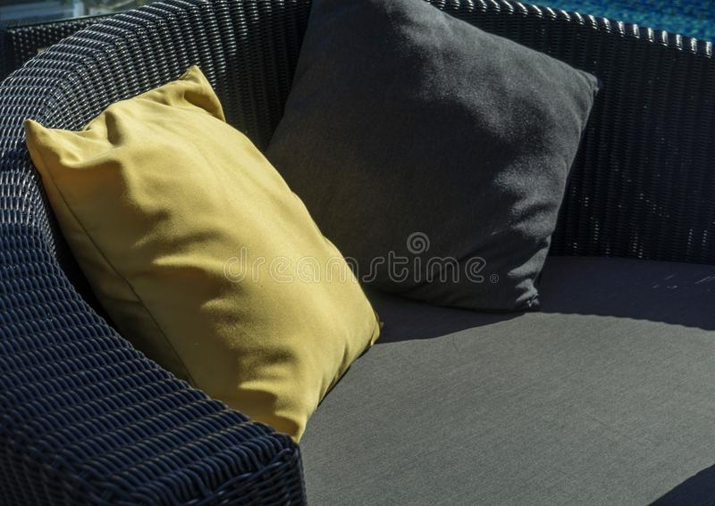 Relaxing chairs with Yellow and dark blue pillow beside swimming pool royalty free stock images