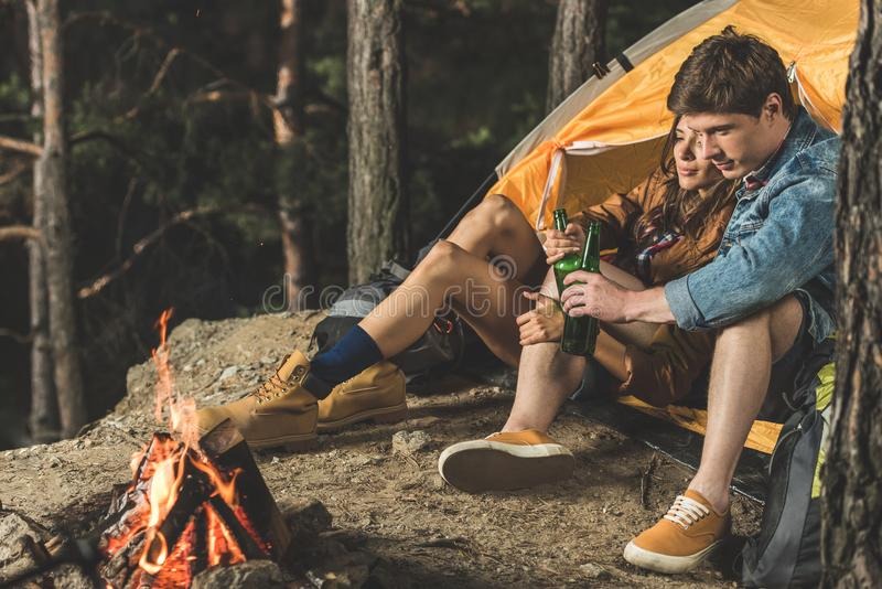 Relaxing couple on hiking trip drinking beer together while sitting. In tent royalty free stock image