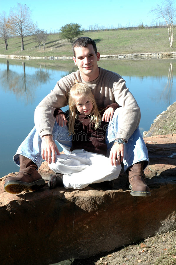 Relaxing with Dad. A little girl leans back on her dad as they sit on a rock in front of a pond at the park. Father and daughter time stock photos