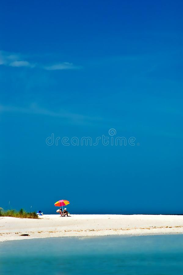 A relaxing day at the beach with sand and blue sky. A relaxing day at the beach with sand, blue sky, turquoise ocean and a colorful umbrella stock photos
