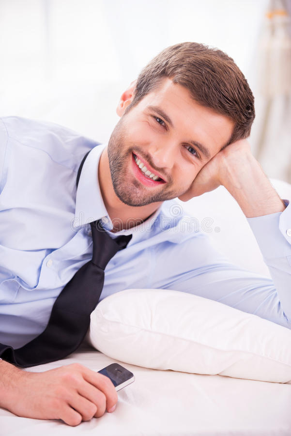 Relaxing after day working. Handsome young man in shirt and tie lying in bed and smiling stock photos
