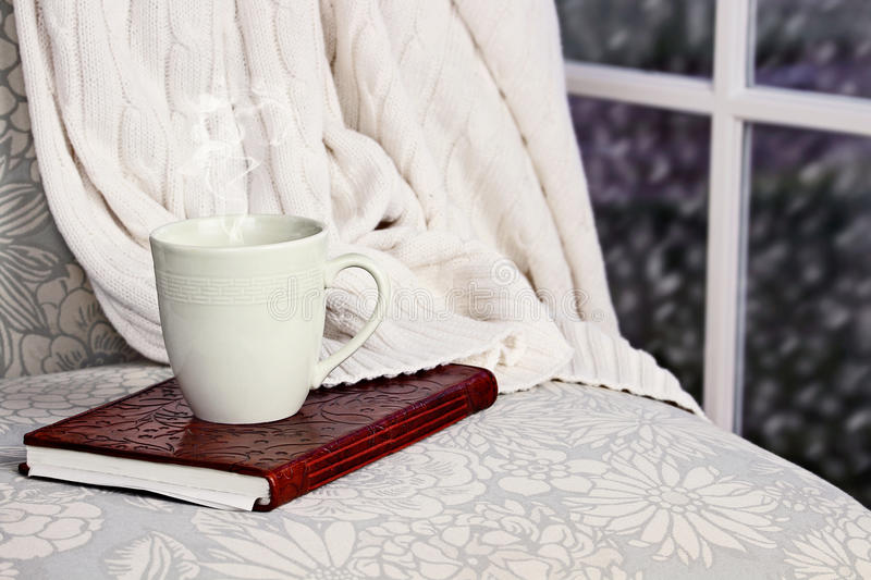 Relaxing Drink and Book. A hot relaxing cup of coffee or cocoa with a book sitting on a comfortable chair with blanket. Extreme shallow depth of field royalty free stock photo