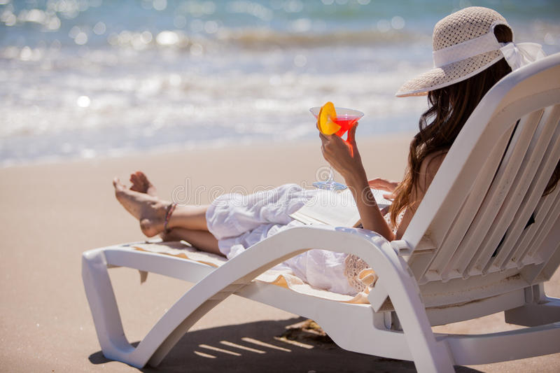 Relaxing with a drink and a book. Young woman relaxing with a good read and a delicious martini with the sound of the waves stock photos