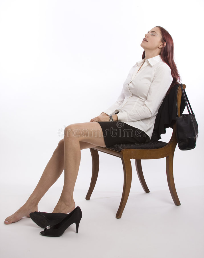 Relaxing at the end of the day. Woman in business attire sitting back with shoes off relaxing stock photography