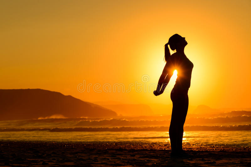 Relaxing exercises on beach at sunset stock photo