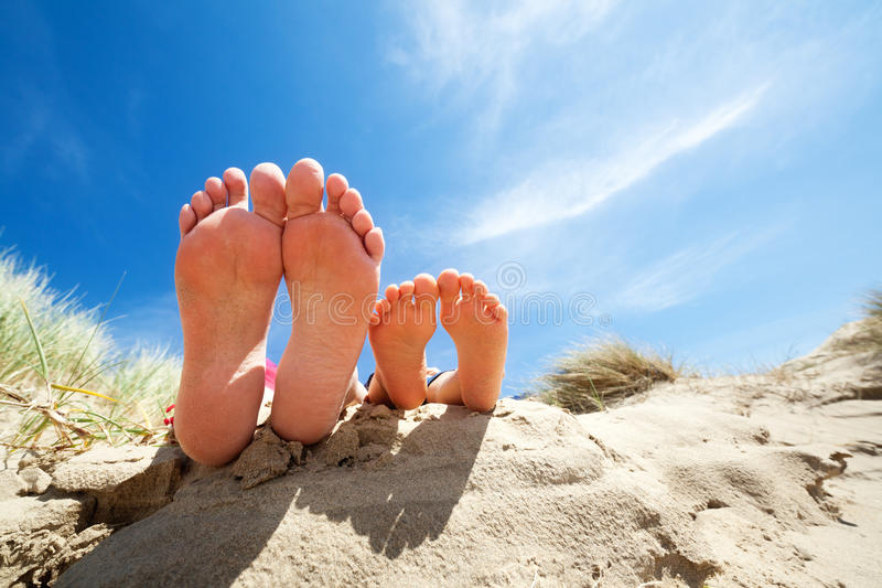 Relaxing feet on the beach. Family feet relaxing and sunbathing on the beach concept for vacation and summer holiday