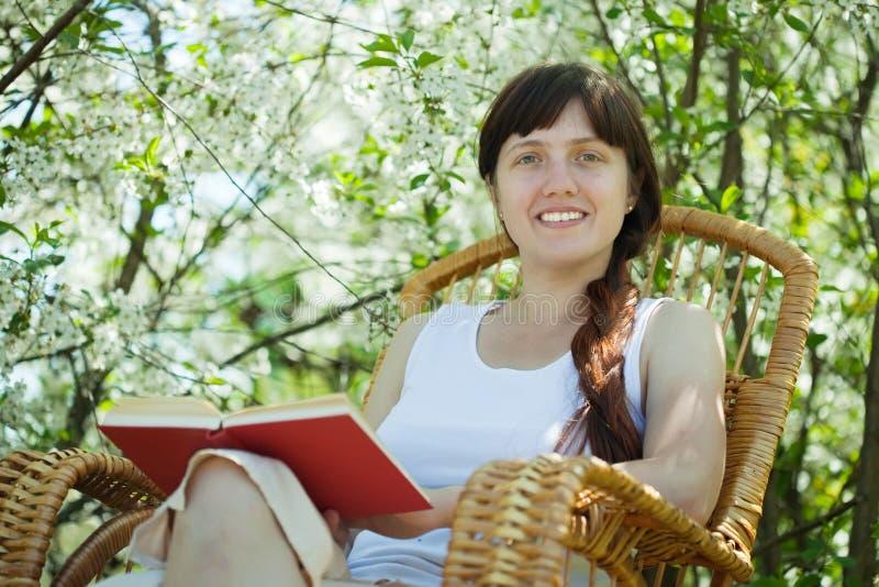 Relaxing girl in bloom garden. Relaxing girl in rocking-chair against bloom garden stock image